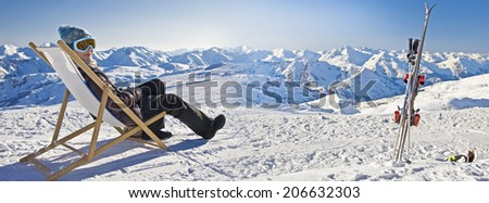 Panorama of a girl sunbathing in a deckchair near a snowy ski slope - stock photo