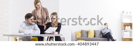 Panorama of a modern, minimalist office with team of colleagues discussing documents at a white desk and a young man talking on the phone in the background - stock photo