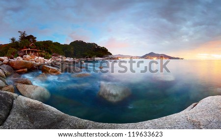 Panorama of a rocky coastline and motion blurred sea surface at twilight. Phuket, Thailand - stock photo