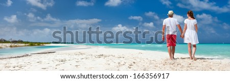 Panorama of a romantic couple at Caribbean beach - stock photo