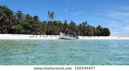 Panorama of a tropical island with lush vegetation and a boat landed on the beach, Caribbean sea, Panama - stock photo