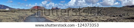 Panorama of a volcanic field with Caldera Colorada volcano in background. Canary Islands, Lanzarote, Spain, Europe. - stock photo