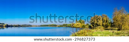 Panorama of autumnal lake and blue sky. - stock photo