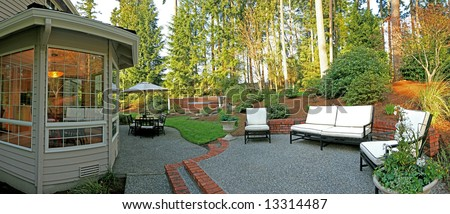 Panorama of backyard with patio set, chairs, and jacuzzi - stock photo