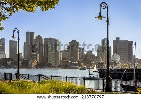 Panorama of Boston in the background in Massachusetts, USA as seen from the Piers Park in Chelsea on a warm and super sunny morning showcasing its Financial District. - stock photo