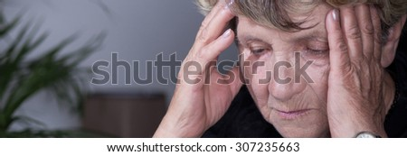 Panorama of despair senior woman having headache - stock photo