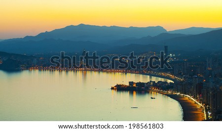 Panorama of evening seaside town with a beach on a background of mountains (Spain, Benidorm) - stock photo