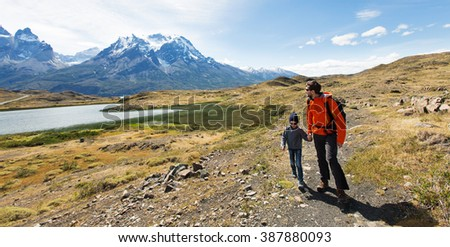 panorama of family of two, father and son, enjoying hiking in torres del paine national park, patagonia, chile - stock photo