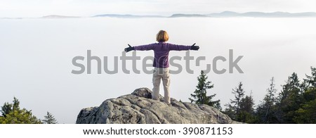 Panorama of freedom traveler woman standing on mountain peak with open arms and enjoying a beautiful nature. Foggy day in the mountains. - stock photo