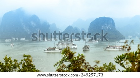 Panorama of Halong Bay in Vietnam with green leaves in foreground. Cliffs and rocks standing out of water with boats floating around. Light fog in distance. Popular travel destination. - stock photo