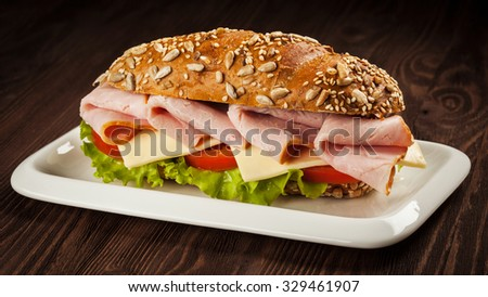 Panorama of ham sandwich with lettuce, cheese, tomato on plate on wooden table - stock photo