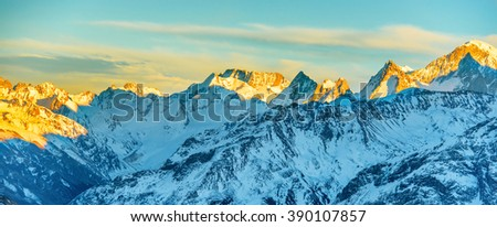 Panorama of high mountains peaks at sunset. Landscape on snow hills - stock photo