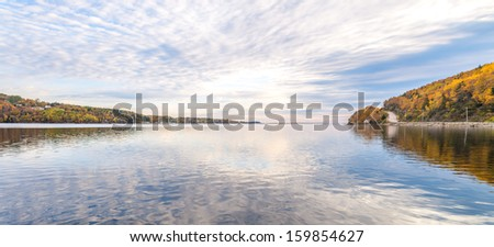 Panorama of lake in the autumn with reflections of clouds - stock photo