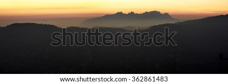 Panorama of Montserrat mountains floated at dusk of a warm light sunset in Spain - stock photo