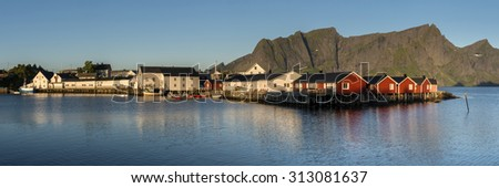 Panorama of mount Olstind above the red fishing houses called Rorbu in town of Hamnoy on Lofoten islands, Norway - stock photo