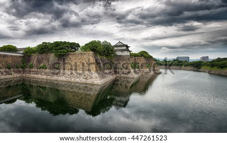 Panorama of Osaka Castle walls and moat. Dramatic skies with mirrored reflection. - stock photo