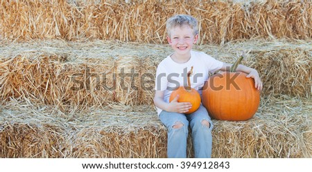 panorama of playful smiling boy enjoying autumn time at pumpkin patch with free space on a side - stock photo