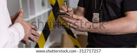 Panorama of police agent talking with witness and making notes - stock photo
