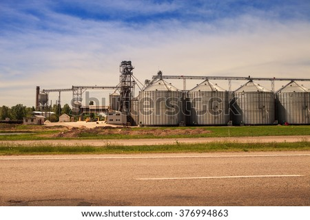 panorama of production yard and metal tank of modern silo in countryside near lake by road - stock photo