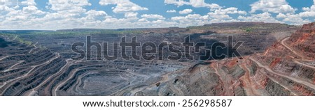 panorama of quarry extracting iron ore with heavy trucks, excavators, diggers and locomotives - stock photo