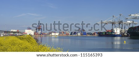 panorama of Rotterdam harbor with a container ship being unloaded - stock photo