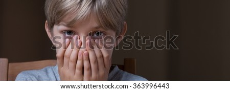 Panorama of scared boy covering his face with hands - stock photo