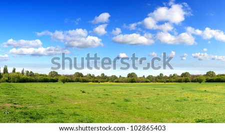 Panorama of sky clouds and grass on meadow - stock photo