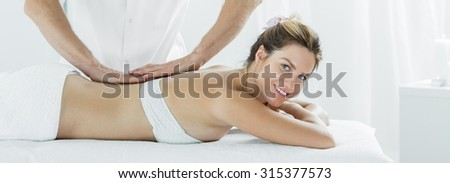 Panorama of smiling beautiful woman during relaxing massage - stock photo