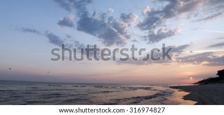panorama of sunset or sunrise on beach with water reflection  - stock photo