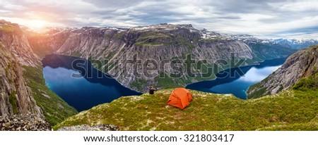 Panorama of sunset over blue mountain lake and man sitting next to orange tent  - stock photo