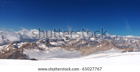 Panorama of the array of the mountains with cloud on background blue sky. Natural composition - stock photo