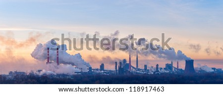 Panorama of the chemical factory throwing out polluting smoke from pipes in the morning sky - stock photo