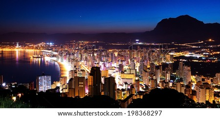 Panorama of the city and the sea coast at sunset on a background of mountains (Spain, Benidorm) - stock photo
