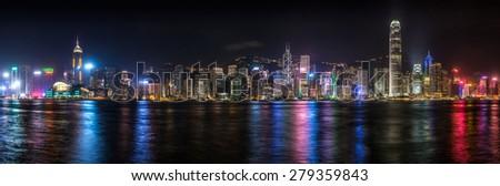 Panorama of the Hong Kong skyline lit up at night along Victoria Harbor. - stock photo