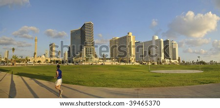 Panorama of The Hotels on Tel-Aviv beach and Jogging man - stock photo