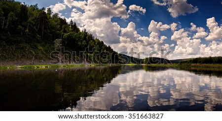 Panorama of the lake amoung hills with many different clouds on the sky - stock photo