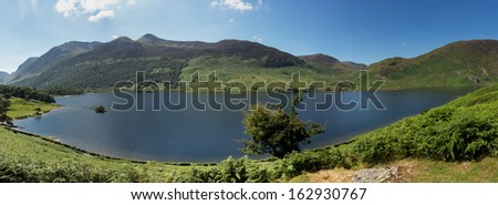 Panorama of the Lake District hills surrounding Crummock Water framed by the trees on the lakeside. Idyllic image from the English Lakes - stock photo