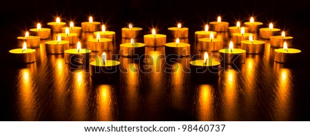 Panorama of the many burning candles with shallow depth of field - stock photo