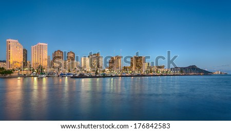 Panorama of the nightime skyline of Honolulu and Waikiki from Ala Moana park as the sun sets and illuminates the facades of the hotels and apartments - stock photo