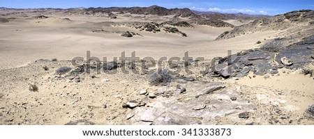 Panorama of the white sand desert in the Skeleton Coast with clear blue sky and mountains in the background, Namibia. - stock photo