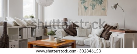 Panorama of white living room with decorative cushions - stock photo