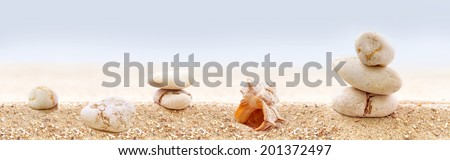 Panorama of zen stones on a sandy beach. - stock photo
