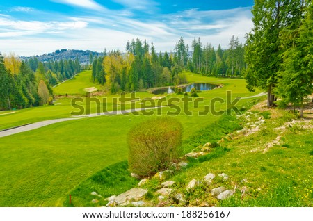 Panorama, outlook at the beautiful golf course in a sunny day with dark blue sky and clouds. Canada, Vancouver. - stock photo