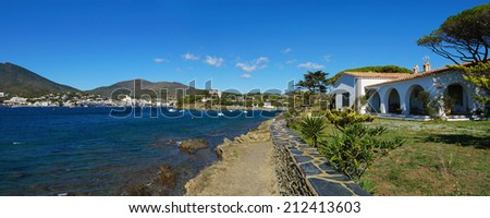 Panorama over the Mediterranean village of Cadaques with seafront house on the right, Costa Brava, Catalonia, Spain - stock photo