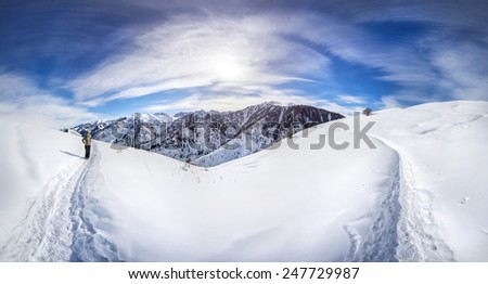 Panorama snowy winter mountains with woman on the trail in Kazakhstan - stock photo
