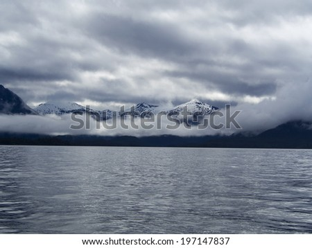 Panorama view of a Range of Snow Mountains in a Cloudy Day with Sunlight. National Park at Sitka, Alaska.  - stock photo