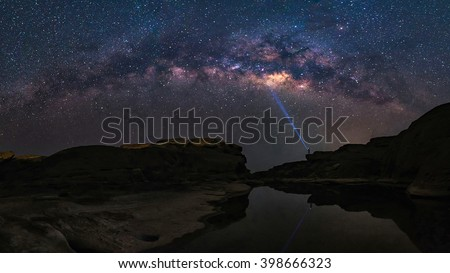 Panorama view of milky way galaxy over the beautiful landscape of the biggest rock field at Sam Pan Boak during night time,Thailand. Sam Pan Boak is known as the Grand Canyon of Thailand. - stock photo