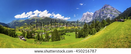 Panorama view to famous Grindelwald valley, green forest, Alps chalets and Swiss Alps (Schreckhorn, Berglistock and Wetterhorn) in the background, Berner Oberland, Switzerland, Europe.  - stock photo