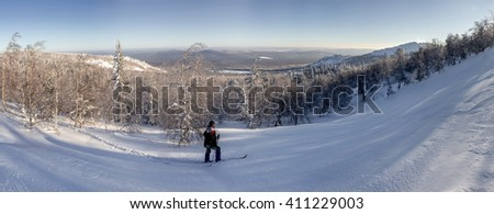 Panorama with group of tourists watching the sunrise in the winter mountains - stock photo