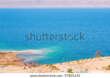 panorama with people on sand beach of Dead Sea, Jordan - stock photo